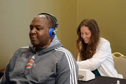 EarQ member, Danielle Mercer, tests the hearing of former players.