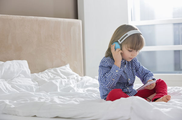 young kid listening to music with headphones